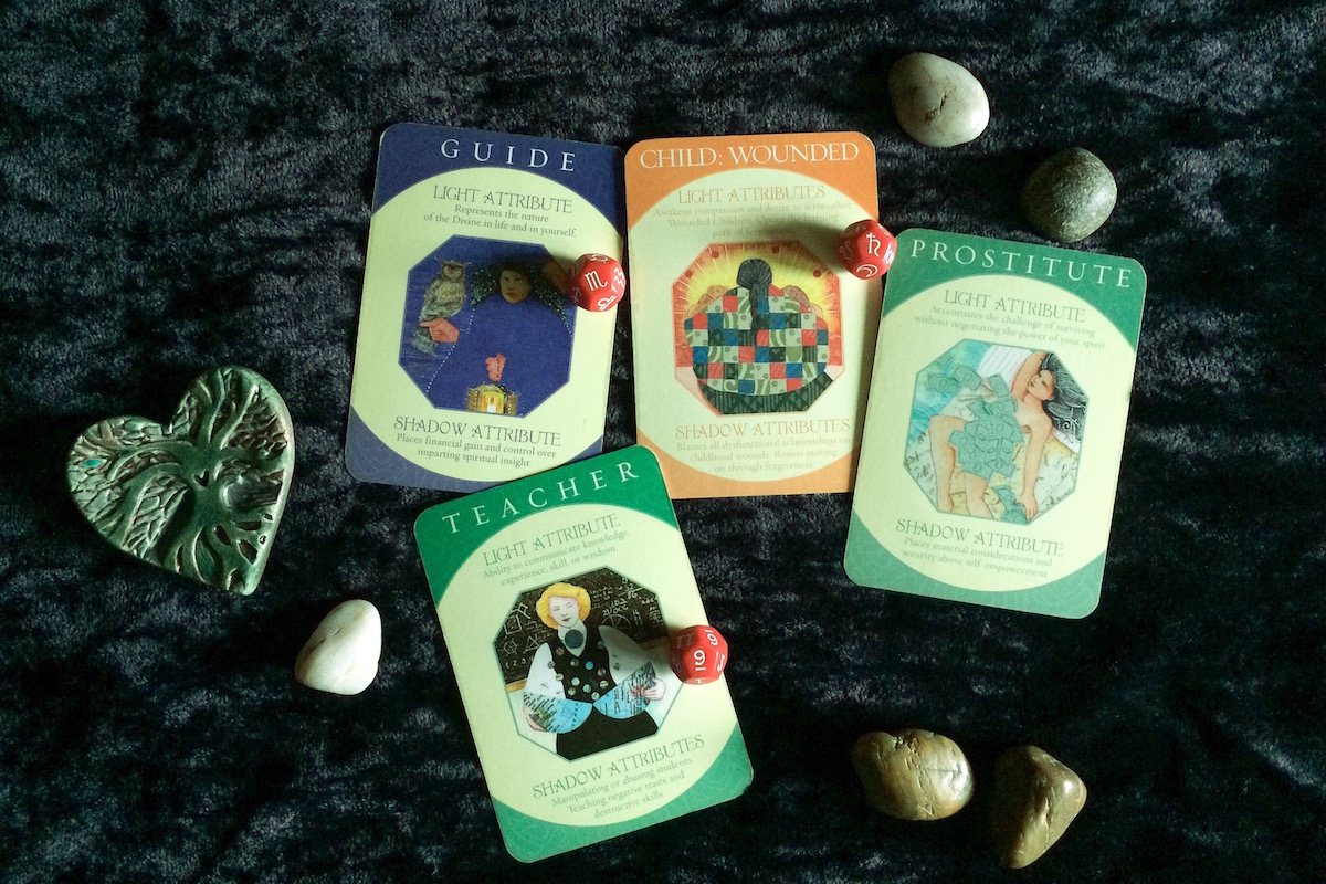 A heart, earth stons, archetype cards for The Guide, the Wounded Child, The Teacher and The Prostitute...with Saturn in the 9th House in Scorpio