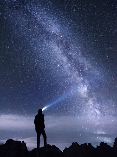 Person with headlamp in the night, its light shining towards the Milky Way